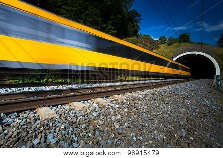 Fast train passing through a tunnel on a lovely summer day (motion blurred image)