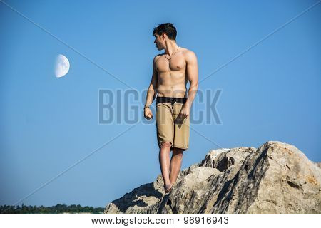 Muscular young man shirtless against the sky with moon