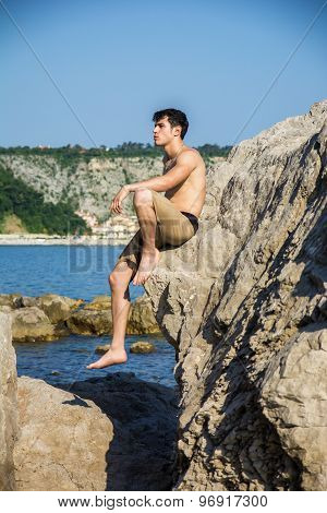 Smiling young man sitting on rock by sea or ocean shore
