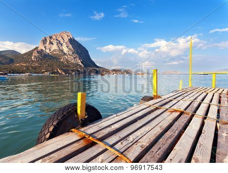 Beautiful Summer Sunset At The Sea With Mountains And Pier