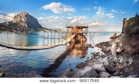 Beautiful Summer Sunset At The Sea With Bridge, Building, Mountains