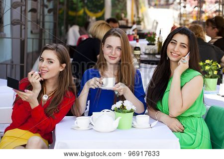 Three young beautiful girls girlfriend drinking tea in a summer cafe