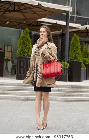 Young beautiful blonde woman in beige short coat posing outdoors in spring street
