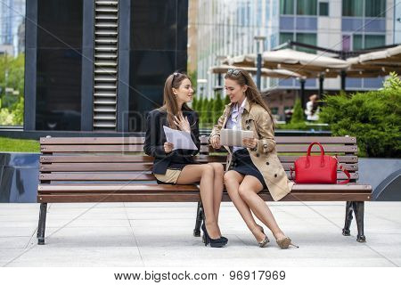 Two young beautiful business women sitting on a bench in the summer city