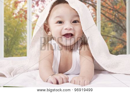 Attractive Baby Laughing On The Bed Alone