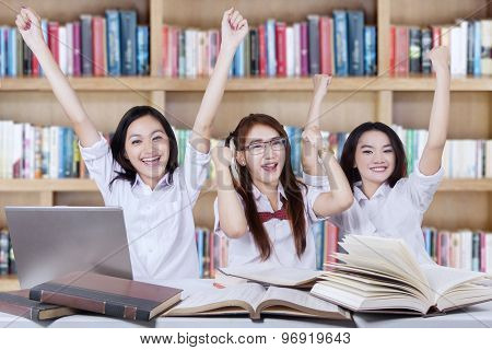 Cheerful Schoolgirls Raise Hands Together In Library