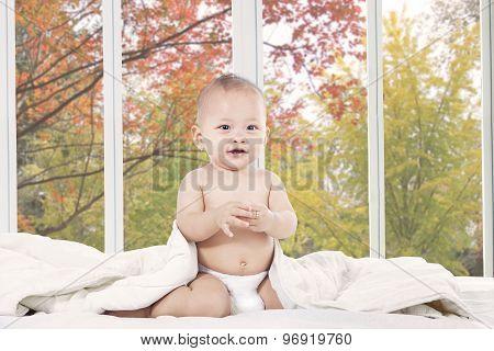 Cute Baby In Bedroom Looking At Camera