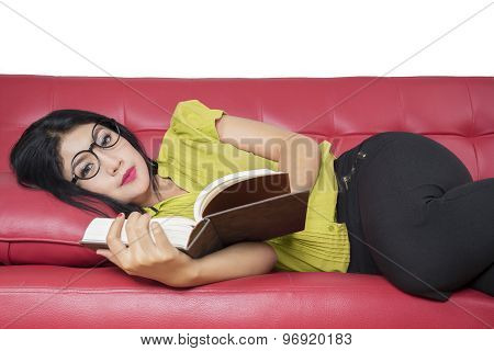Excited Woman Resting On Sofa While Reading Book