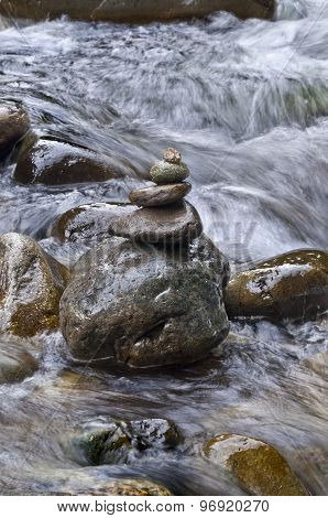 Closeup of stacked rocks in flowing water