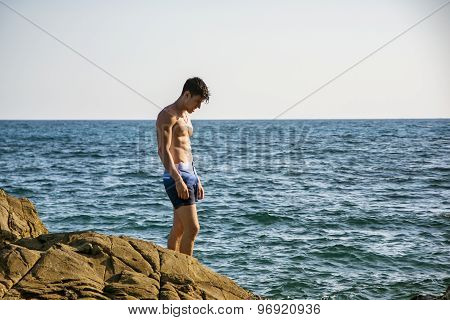 Muscular young man on rock by sea