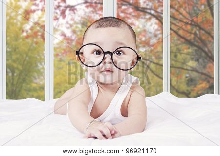Male Baby With Glasses Lying On Bed