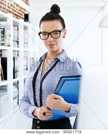 Portrait of pretty young secretary holding folders, looking at camera.