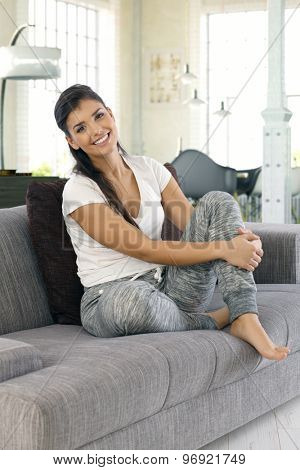 Happy young woman smiling, looking at camera, sitting on sofa at home.