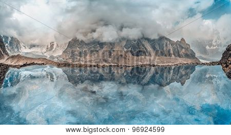 Beautiful mountain lake with reflection under the clouds