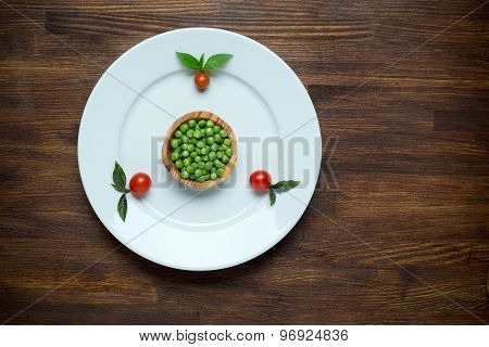 Healthy food theme: green peas on a plate with tomato cherry. Wooden table background