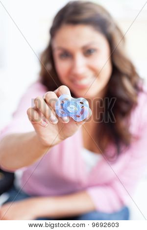Portrait Of A Young Mother Showing A Blue Dummy To The Camera Sitting In The Living-room