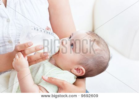 Peaceful Baby Boy Lying In His Mother's Arms Drinking Milk For Lunch