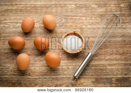 Eggs with beater and salt on wooden table
