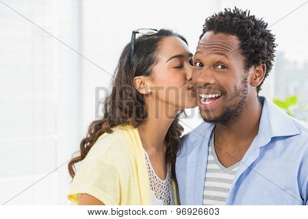Portrait of a woman kissing her colleague in the office