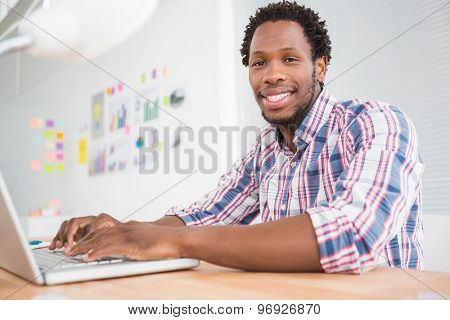 Young businessman types on the laptop and looks at the camera in the office