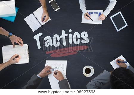 The word tactics and business meeting against blackboard