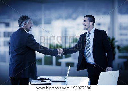 Businessmen shaking hands against office