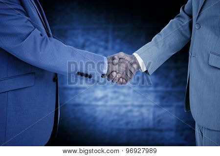 Side view of shaking hands against dark grey room