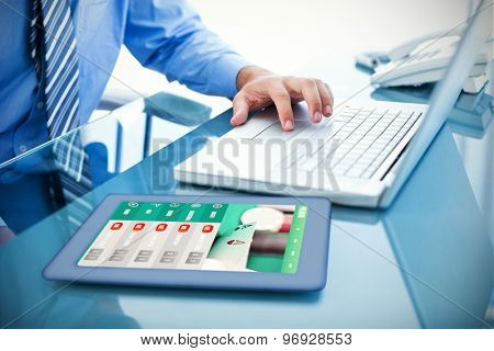 Businessman using his laptop against gambling app screen