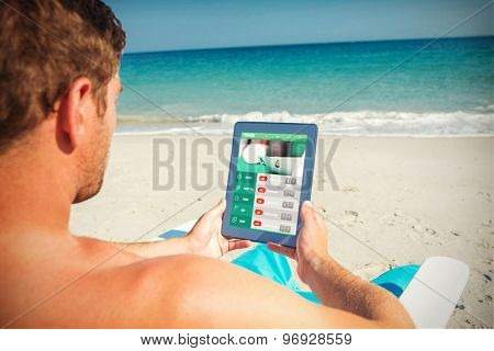 Man using digital tablet on deck chair at the beach against gambling app screen