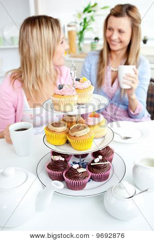 Two Cute Friends Eating Cupcakes Sitting In The Kitchen At Home