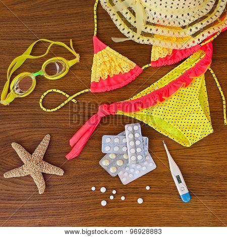 Summer beach accessories and medicine on the table.