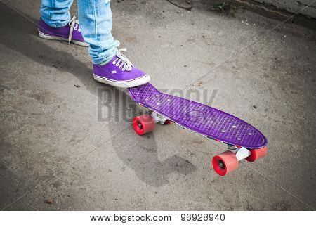 Young Skateboarder Feet In Gumshoes And Jeans