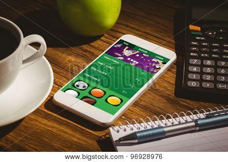 Gambling app screen against smartphone on table