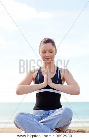 Young Caucasian Woman Doing Yoga Sitting On The Beach During A Sunny Day