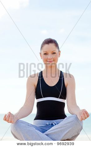 Attractive Woman Doing Yoga Exercises Sitting On The Beach