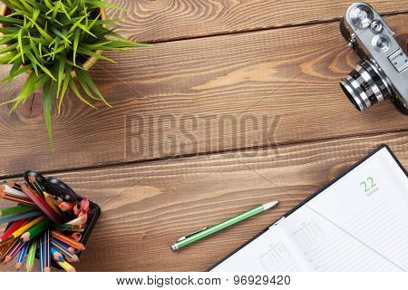 Office desk table with camera, supplies and flower. Top view with copy space