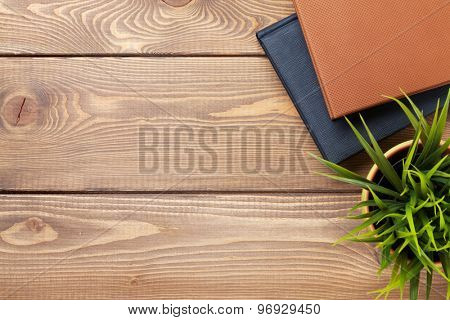Office desk table with flower and notepad. Top view with copy space