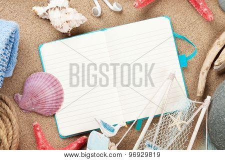 Travel and vacation notepad with items over sea sand. Top view with copy space