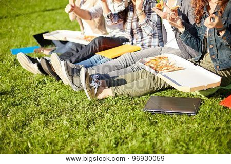 education, food, people and friendship concept - close up of happy teenage students eating pizza and sitting on grass