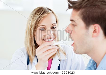 Portrait Of A Female Doctor Taking A Saliva Sample Of A Male Patient With Cotton-bud
