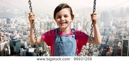 summer, childhood, leisure, friendship and people concept - happy little girl swinging on swing over city background