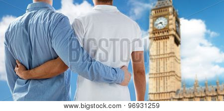 people, homosexuality, same-sex marriage, travel and love concept - close up of happy male gay couple hugging from back over big ben tower in london background