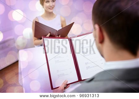 restaurant, food, eating and holiday concept - close up of couple with menu choosing dishes at restaurant over violet holidays lights background