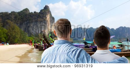people, homosexuality, same-sex marriage, travel and love concept - close up of happy male gay couple hugging from back over thailand beach background