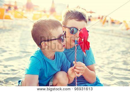 Little Boys Blowing Pinwheel In Sunset