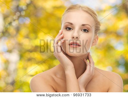 beauty, people and body care concept - beautiful young woman touching her face over yellow autumn background
