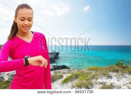 sport, fitness, technology, healthcare and people concept - smiling young african american woman with heart rate watch over beach background