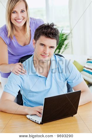 Young Man Using A Laptop Sitting At A Table With His Girlfriend Behind Both Smiling At The Camera