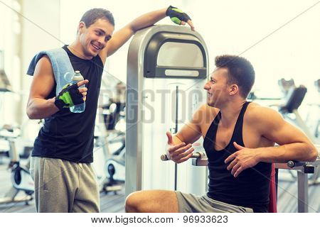 sport, fitness, equipment, lifestyle and people concept - smiling men with bottle of water exercising on gym machine