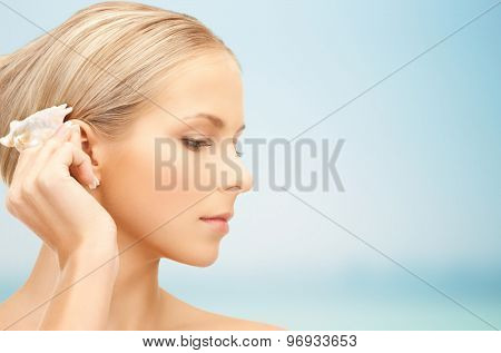 people, beauty and beach concept - beautiful woman with seashell over blue background